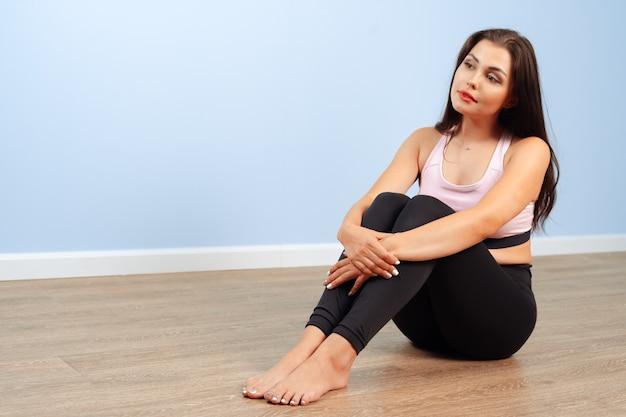 Donna adatta in abiti sportivi che si siede sul pavimento in una palestra