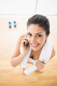Donna adatta sul telefono che sorride alla macchina fotografica