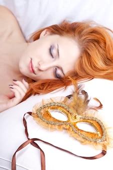 Donna addormentata vicino alla maschera di carnevale.
