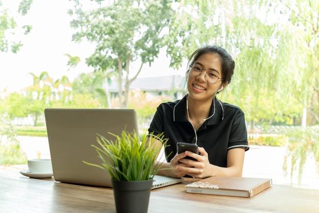 Donna adolescente asiatica con l'ubicazione del computer portatile e del trasduttore auricolare in caffè.