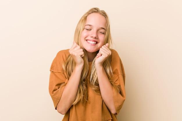 Donna adolescente carina e naturale alzando il pugno, sentirsi felice e di successo. concetto di vittoria.