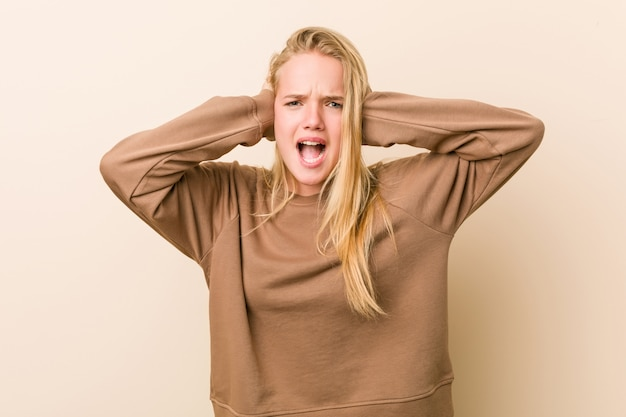 Donna adolescente carina e naturale che copre le orecchie con le mani cercando di non sentire un suono troppo forte.