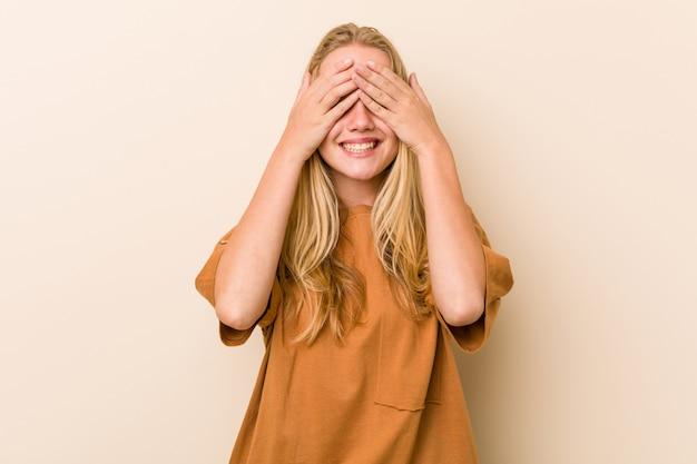 Donna adolescente carina e naturale copre gli occhi con le mani, sorride ampiamente aspettando una sorpresa.