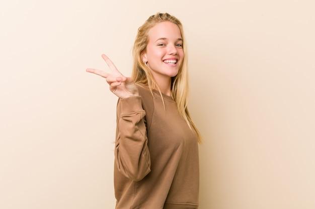 Donna adolescente carina e naturale gioiosa e spensierata mostrando un simbolo di pace con le dita.