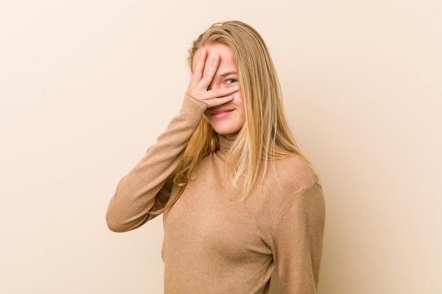 Donna adolescente carina e naturale lampeggia alla macchina fotografica attraverso le dita, imbarazzato volto coprente.