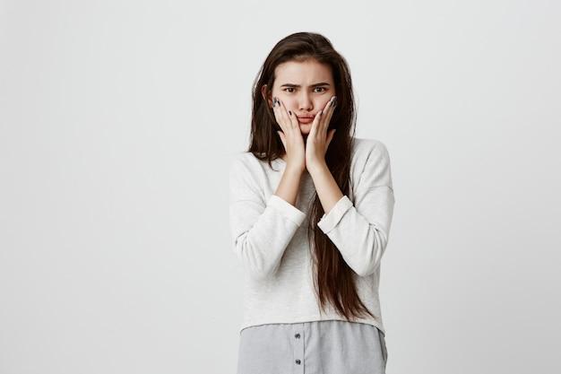 Donna adolescente castana emotiva stordita scioccata tiene le mani sulle guance, essere turbata