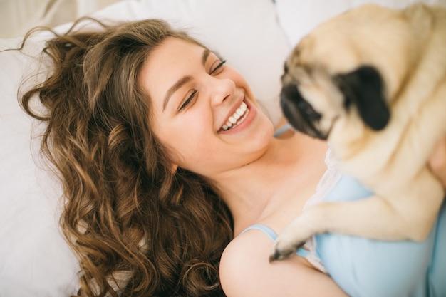 Donna adorabile che abbraccia il suo cane del carlino a letto