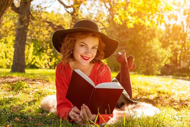 Donna adorabile che legge un libro nel parco di autunno che si siede sull'erba