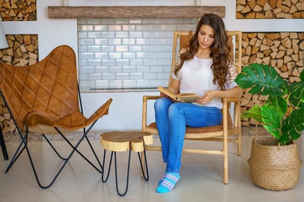 Donna adorabile che si siede su una sedia che legge un libro