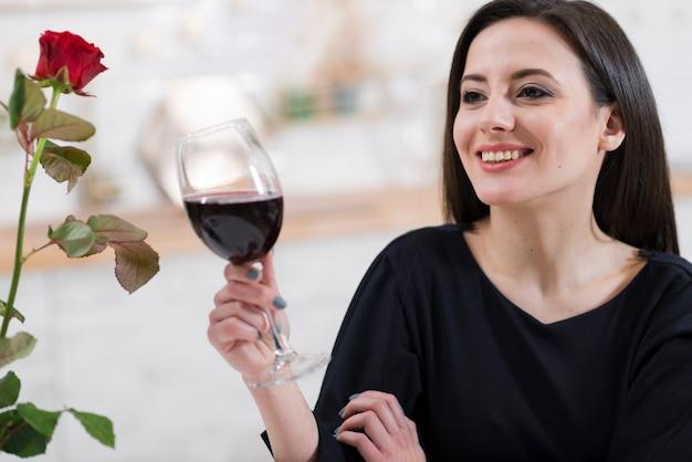Donna adorabile che tiene un bicchiere di vino rosso