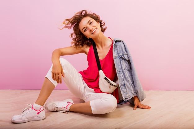Donna adorabile con i capelli ondulati corti che si siedono sul pavimento sopra il rosa