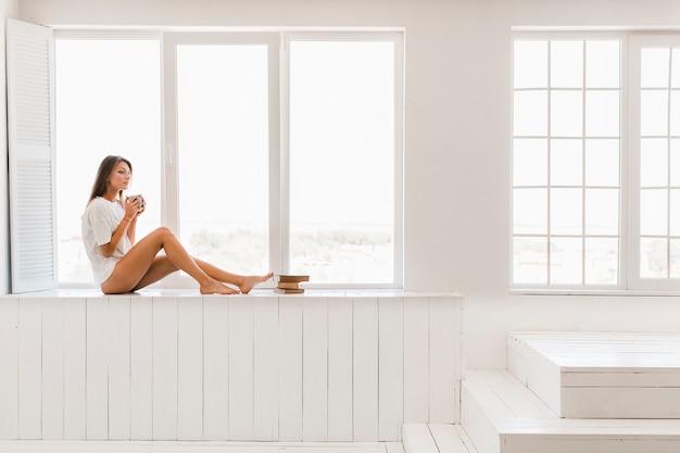 Donna adorabile con la bevanda che si siede vicino alla finestra