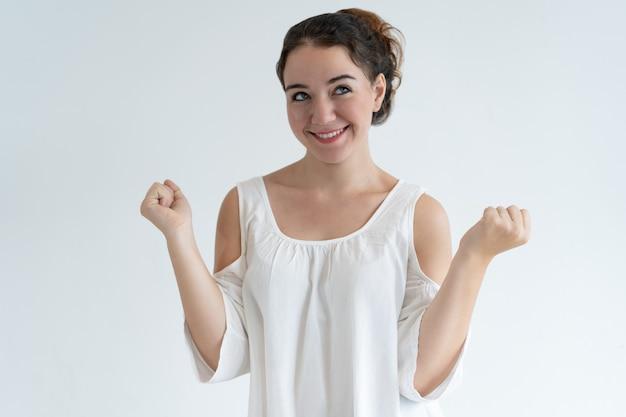 Donna adorabile felice che pompa i pugni e che celebra successo