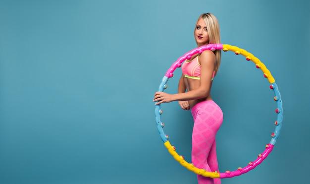 Donna adorabile in abiti sportivi rosa che posano con il cerchio