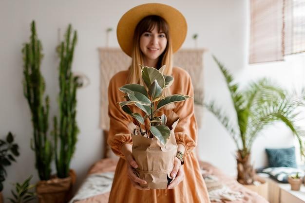 Donna adorabile in vestito di lino e cappello di paglia che posano in appartamento di stile di boho