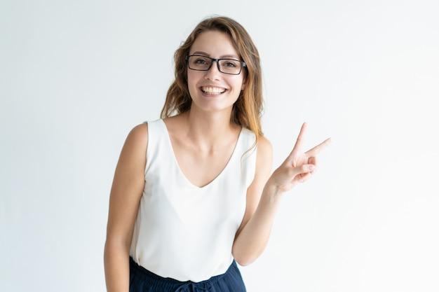 Donna adorabile sorridente che mostra il segno di vittoria e che esamina macchina fotografica