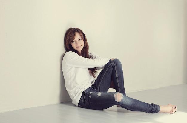 Donna adulta adorabile e affascinante che si siede sul pavimento