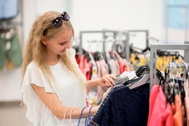 Donna adulta alla moda che controlla i vestiti