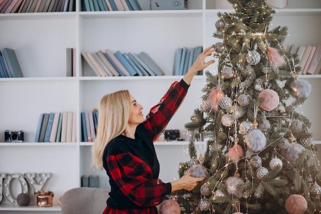 Donna adulta che decora l'albero di natale