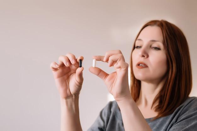 Donna adulta che esamina le pillole in bianco e nero