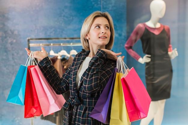Donna adulta che posa con i sacchetti della spesa