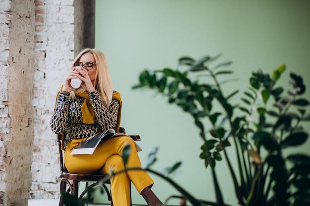 Donna adulta che si siede nella sedia che beve caffè e che legge rivista
