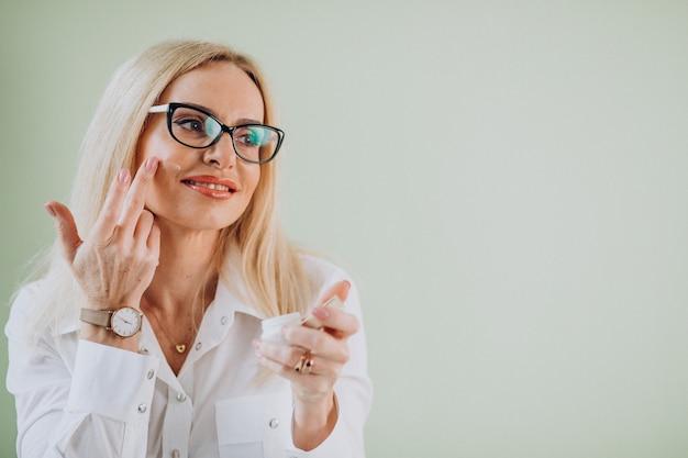 Donna adulta che usando la crema anti invecchiamento