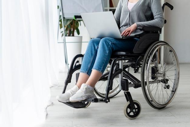Donna adulta del primo piano che lavora ad un computer portatile