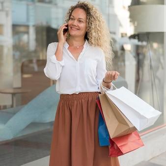 Donna adulta di vista frontale che tiene i sacchetti della spesa
