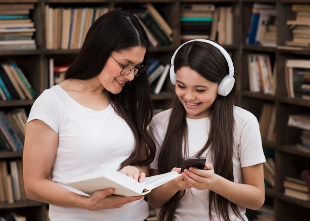 Donna adulta di vista frontale con la ragazza alla biblioteca