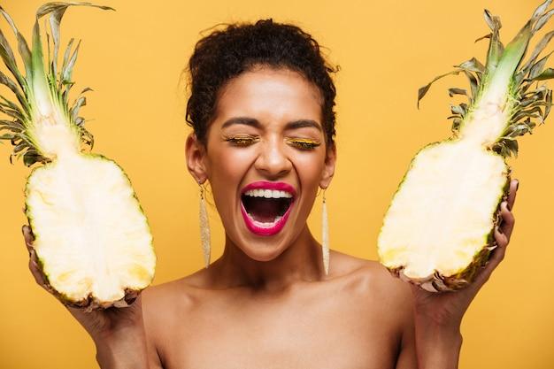 Donna adulta felice con l'acconciatura afro e il trucco alla moda che tiene due metà di ananas appetitoso fresco, isolato sopra la parete gialla