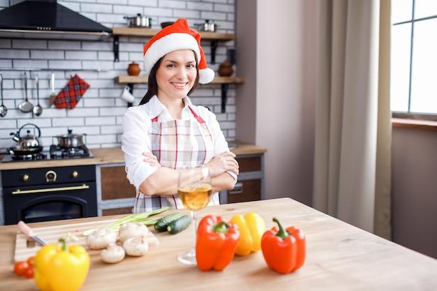 Donna adulta felice positiva che posa sulla macchina fotografica in cucina
