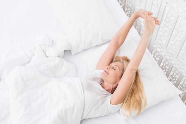 Donna adulta graziosa del primo piano che sveglia