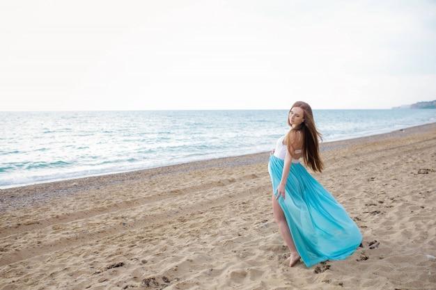 Donna adulta incinta sulla riva di un mare caldo estivo