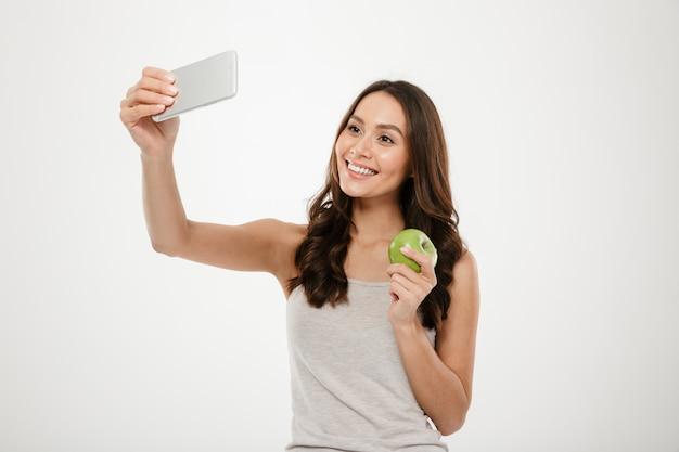 Donna affascinante attraente che fa selfie sul cellulare d'argento e che tiene mela verde succosa, isolata sopra la parete bianca