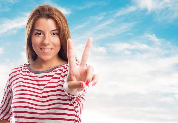 Donna affascinante che mostra il segno di pace