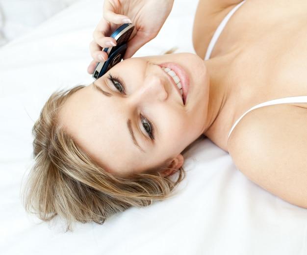 Donna affascinante che parla sul telefono che si trova su un letto