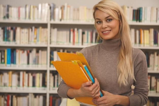Donna affascinante che studia alla biblioteca