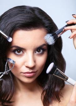 Donna affascinante con cosmetici per il viso.
