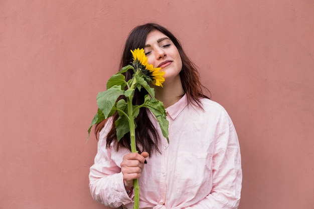 Donna affascinante con girasole in fiore