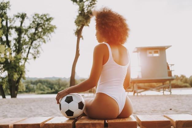 Donna africana adatta sulla spiaggia alla luce del tramonto.