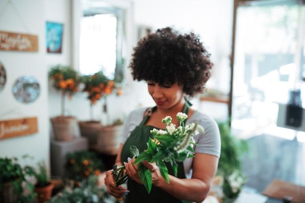 Donna africana afro che tiene mazzo di fiori