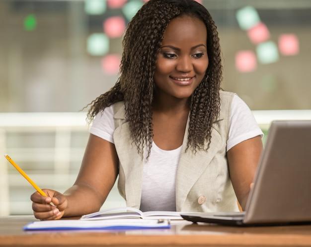 Donna africana attraente che si siede al tavolo.
