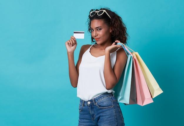 Donna africana che mostra una carta di credito e sacchetti della spesa