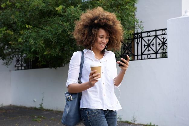 Donna africana con capelli ricci che cammina con il telefono cellulare