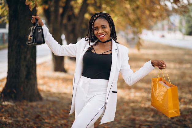 Donna africana con i sacchetti della spesa gialli in parco