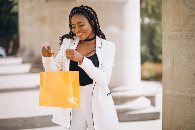Donna africana con i sacchetti della spesa gialli