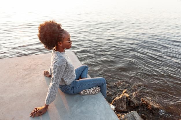 Donna africana dell'angolo alto che si siede vicino all'acqua