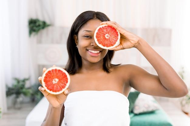 Donna africana di bellezza con il pompelmo arancio dell'agrume con l'ente sano della pelle. vitamina fresca attraente.