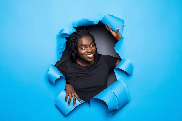Donna africana di sorriso dei giovani che posa dal foro della carta blu